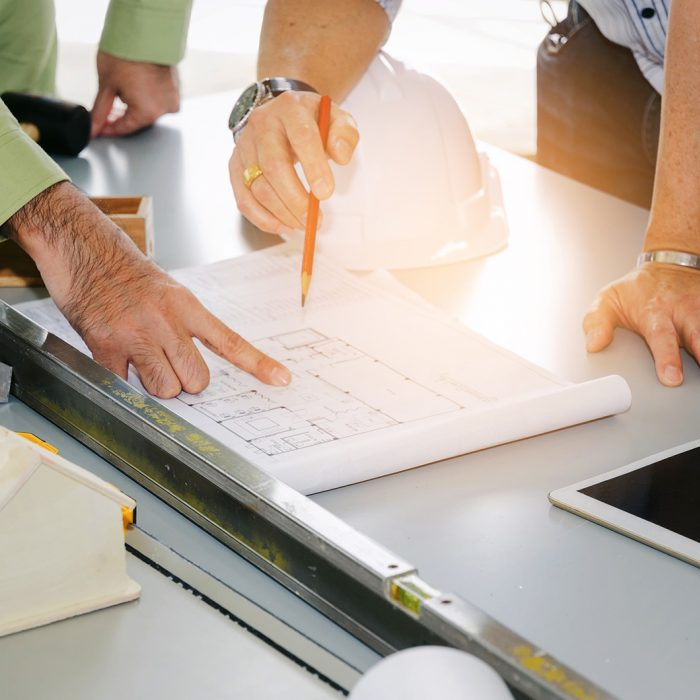 Engineer, technician and architect planning about building plan with blueprint, safety helmet, construction tools on conference table at construction site, business, industry, construction